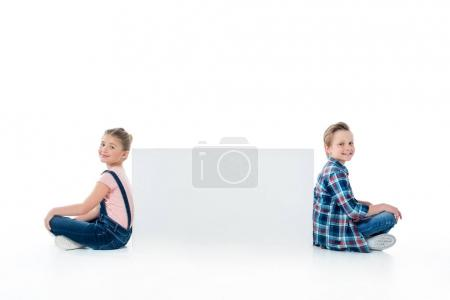Photo for Smiling cute kids sitting with blank banner and smiling at camera - Royalty Free Image