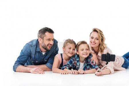 Photo pour Famille heureuse avec deux enfants, emportant selfie smartphone isolé sur blanc - image libre de droit