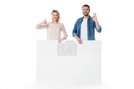 Photo for Happy young couple holding blank banner and gesturing successful sign isolated on white - Royalty Free Image