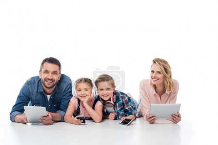 Photo for Smiling family with various digital devices looking at camera isolated on white - Royalty Free Image