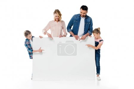 Photo for Smiling parents and kids pointing at blank banner isolated on white - Royalty Free Image