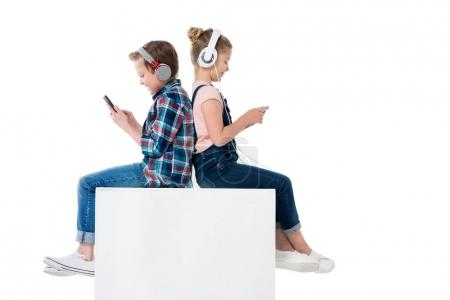 Photo for Children using smartphones in headphones while sitting on cube together isolated on white - Royalty Free Image