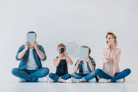 Photo for Casual family using digital devices while sitting on the floor - Royalty Free Image
