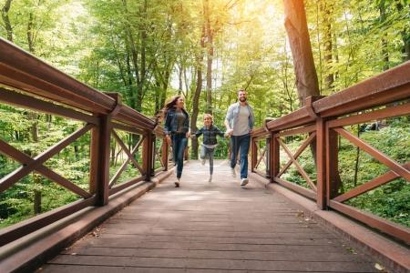 Photo for Young happy interracial family running through the wooden bridge in sunny forest - Royalty Free Image
