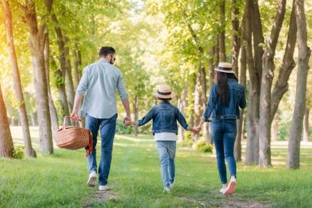 Photo for Rear view of young family with picnic basket walking in sunny forest - Royalty Free Image