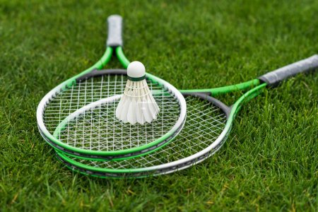 Photo for Close up of shuttlecock on badminton rackets lying on green grass - Royalty Free Image