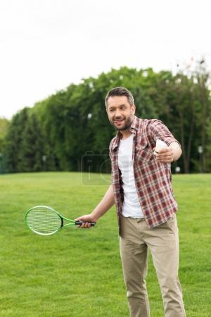 Photo pour Homme gai, sortir la langue pendant la lecture de badminton dans le parc - image libre de droit