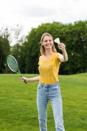 Photo pour Blonde femme souriante tenant la raquette de badminton et volant dans le parc - image libre de droit