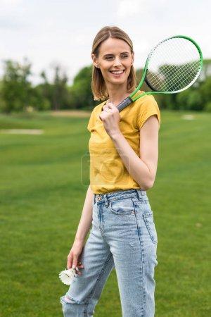 Photo pour Femme souriante tenant la raquette de badminton et le volant tout en regardant loin - image libre de droit