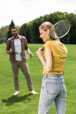 Photo for Happy young couple playing badminton on green meadow - Royalty Free Image