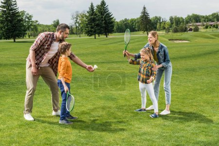 Photo for Parents teaching little kids how to play badminton at park - Royalty Free Image