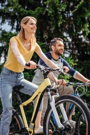 Photo for Young smiling couple riding bicycles together in park - Royalty Free Image