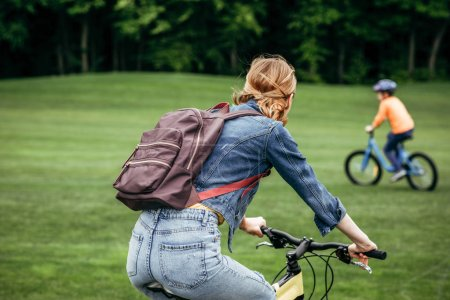 Photo for Rear view of woman with backpack riding bicycle in park - Royalty Free Image