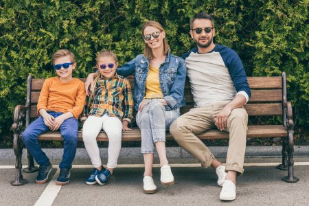 family sitting on bench
