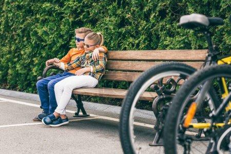 Foto de Niña abrazando niño descansando juntos en la banca en el Parque - Imagen libre de derechos