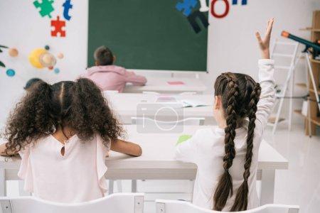 Photo pour Vue de dos des élèves assis aux bureaux et écolière levant la main à la leçon - image libre de droit