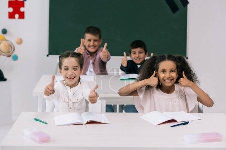 Photo pour Des écoliers multiethniques joyeux montrant les pouces levés alors qu'ils étaient assis aux bureaux dans la salle de classe - image libre de droit