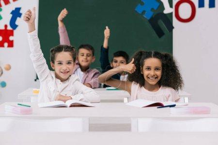 Foto de Escolares multiétnicos alegre mostrando los pulgares mientras está sentado en el escritorio en el aula - Imagen libre de derechos