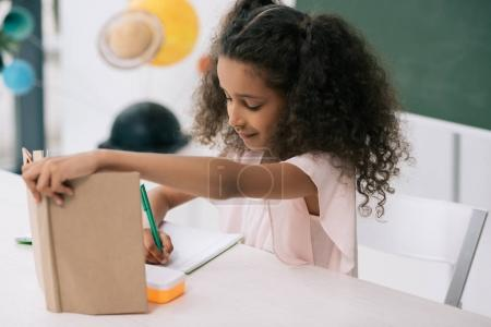 Photo for Focused african american schoolgirl holding textbook and writing exercise at lesson - Royalty Free Image