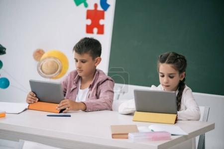 Photo pour Concentré d'écolier et écolière à l'aide de tablettes numériques tout en étant assis au comptoir, en salle de classe - image libre de droit