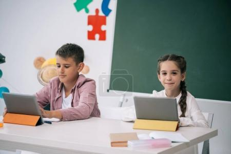 Schoolkids studying with digital tablets