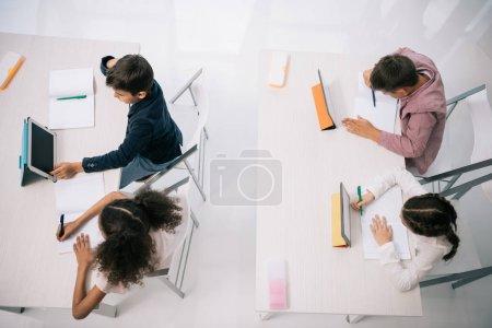 Photo pour Vue aérienne des élèves à l'aide de tablettes numériques tout en étant assis à un bureau dans la salle de classe - image libre de droit