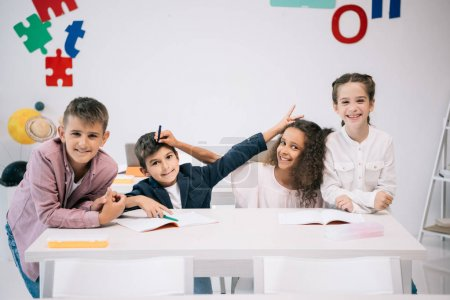 Photo for Cheerful multiethnic students having fun and smiling at camera in classroom - Royalty Free Image