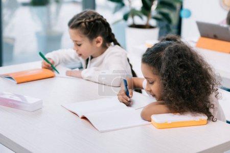Photo pour Adorables écolières multiethniques écrivant et étudiant au bureau en classe - image libre de droit