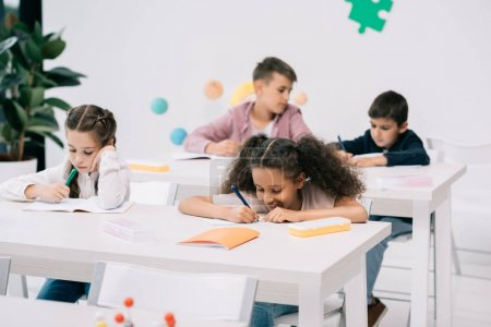 Photo for Multiethnic group of schoolkids writing in exercise books and studying together in classroom - Royalty Free Image