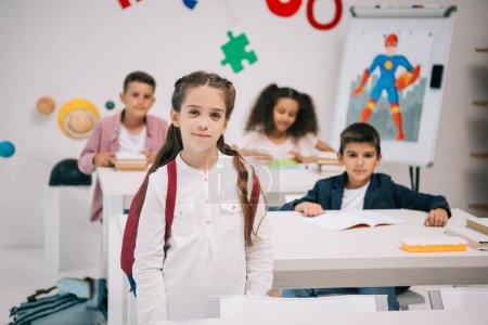 Photo pour Écolière souriante mignonne avec des camarades de classe multiethniques regardant la caméra dans la salle de classe - image libre de droit