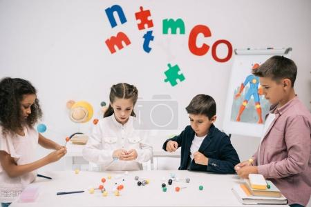 Photo for Multiethnic pupils of elementary school working with molecular model at chemistry class - Royalty Free Image