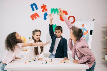 Photo for Multiethnic schoolkids giving high five while studying with molecular model in classroom - Royalty Free Image