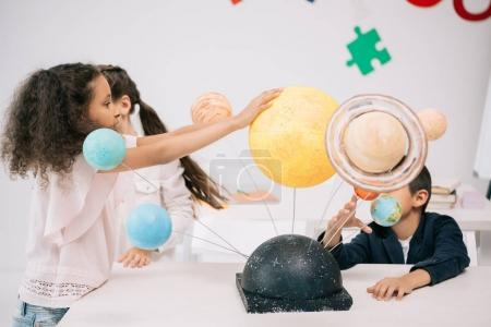 Photo for Multiethnic group of schoolchildren working with solar system model in classroom - Royalty Free Image