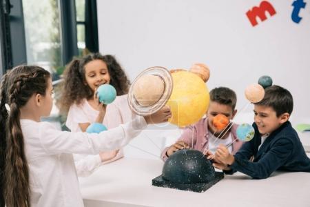 Photo pour Groupe multiethnique d'écoliers travaillant avec le modèle du système solaire en classe - image libre de droit