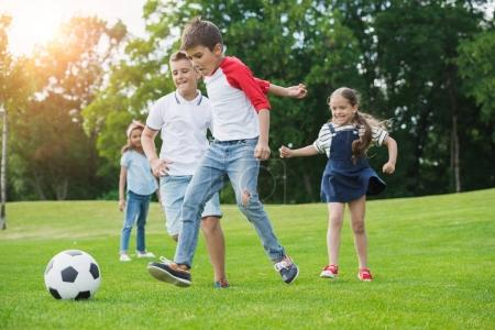 Photo for Cute happy multiethnic kids playing soccer with ball in park - Royalty Free Image