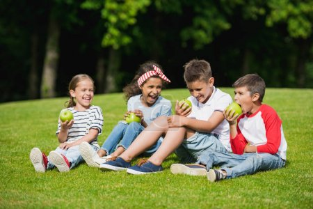 Photo for Happy multiethnic children eating green apples while sitting together on green grass - Royalty Free Image
