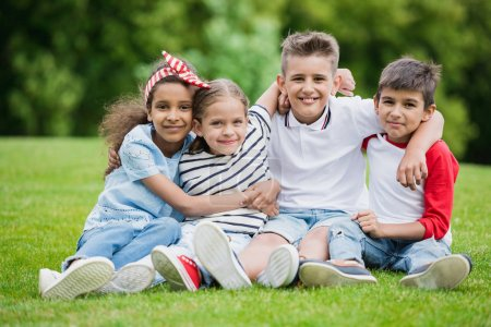 Photo for Happy multiethnic kids sitting embracing and smiling at camera in park - Royalty Free Image