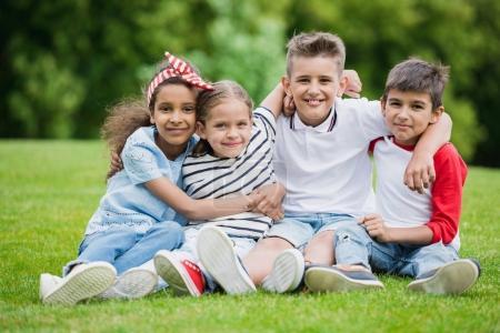 Photo pour Heureux enfants multiethniques assis embrassant et souriant à la caméra dans le parc - image libre de droit