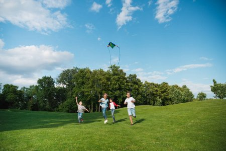 Photo for Cheerful multiethnic kids playing together while running with kite in park - Royalty Free Image
