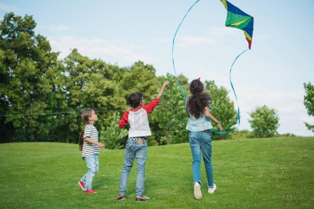 Photo for Adorable happy children playing with kite on green grass in park - Royalty Free Image