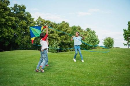 Photo for Cheerful multiethnic kids playing with kite on green lawn in park - Royalty Free Image