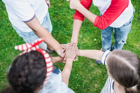 Photo for Cropped shot of children stacking hands while standing on green grass - Royalty Free Image