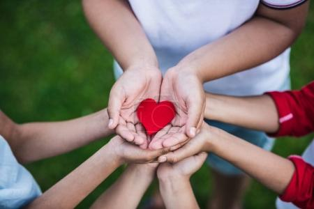 Photo for Close-up partial view of children holding red heart symbol outdoors - Royalty Free Image