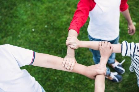 Photo for Close-up partial view of children holding hands while standing on green lawn in park - Royalty Free Image
