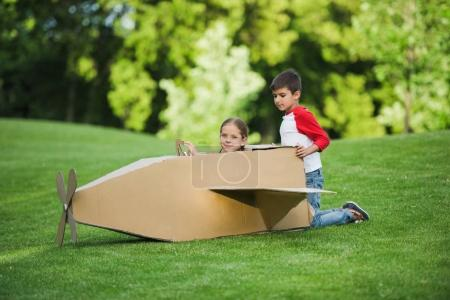 Photo for Adorable little kids playing with cardboard airplane in green park - Royalty Free Image
