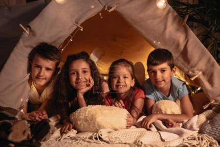 multiethnic children resting in tent