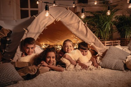 multicultural children resting in tent at home