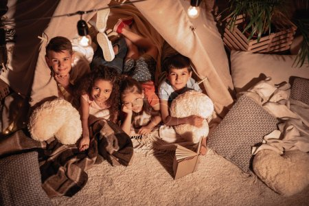 Multiethnic children resting in tent at home