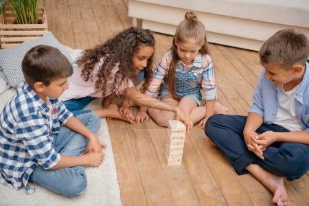 Photo for Multicultural group of children playing blocks wood game together at home - Royalty Free Image