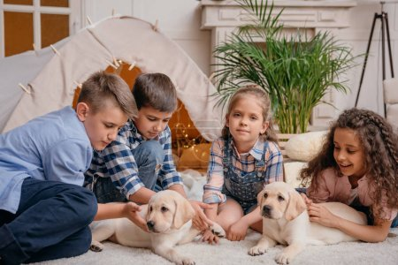 multiethnic children with labrador puppies